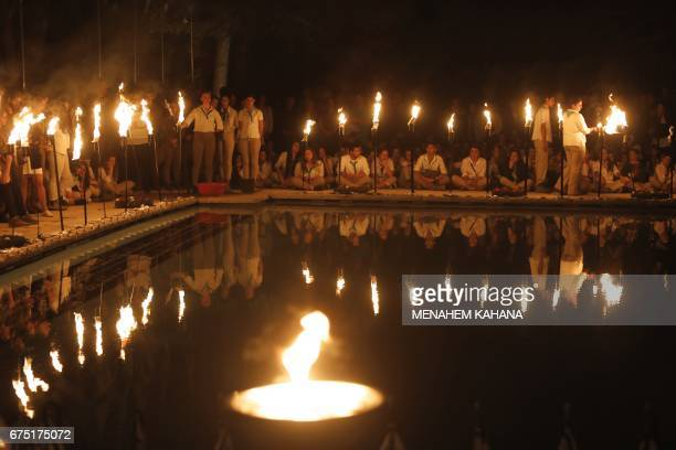 Israeli scouts light torches on April 30 during a ceremony at the Mount Herzel military cemetery in Jerusalem at the start of Remembrance Day...