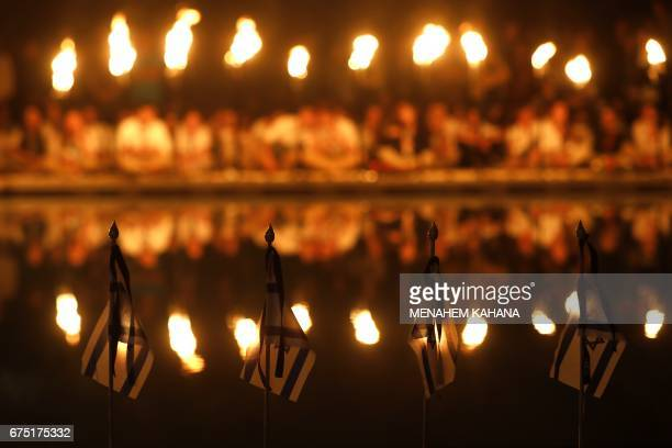 TOPSHOT Israeli scouts sit behind lit torches on April 30 during a ceremony at the Mount Herzel military cemetery in Jerusalem at the start of...