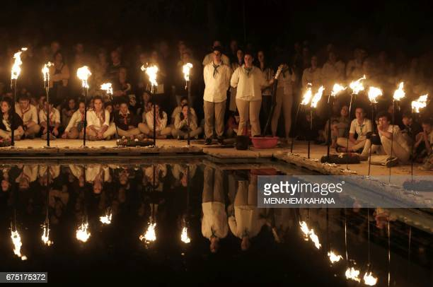 Israeli scouts sit behind lit torches on April 30 during a ceremony at the Mount Herzel military cemetery in Jerusalem at the start of Remembrance...