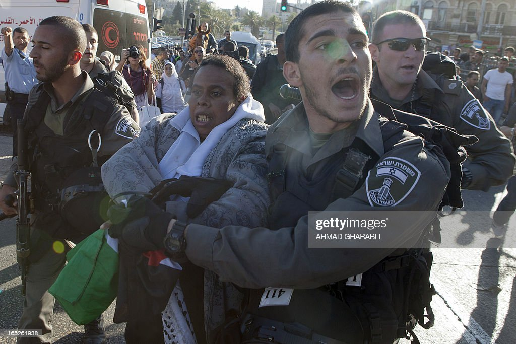 Israeli security arrest a Palestinian woman as clashes broke out during a protest following the death of a Palestinian prisoner being held in an Israeli jail on April 2, 2013, at the entrance of Jerusalem's Old City next to the Damascus Gate. The Palestinian leadership blamed Israel for the death of Maisara Abu Hamdiyeh, a long-term prisoner with cancer, hiking tensions over a tinderbox issue closely followed on the Palestinian street. AFP PHOTO/AHMAD GHARABLI