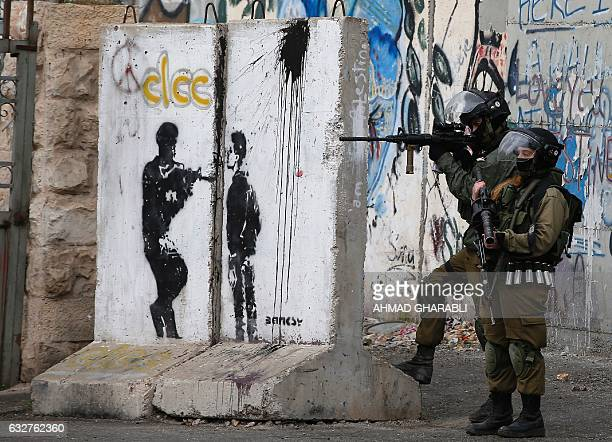 TOPSHOT Israeli security force hold a position during clashes with Palestinian stone throwers following a demonstration demanding that Israeli...
