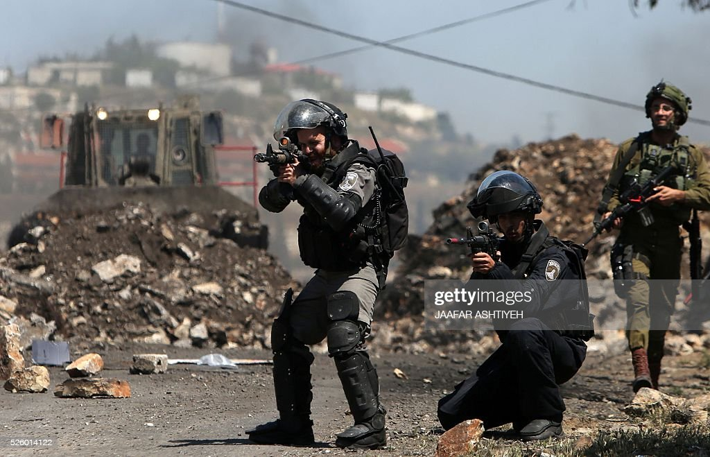 Israeli security forces aim at Palestinian protesters during clashes following a demonstration against the expropriation of Palestinian land by Israel on April 29, 2016 in the village of Kfar Qaddum, near Nablus, in the occupied West Bank. / AFP / JAAFAR