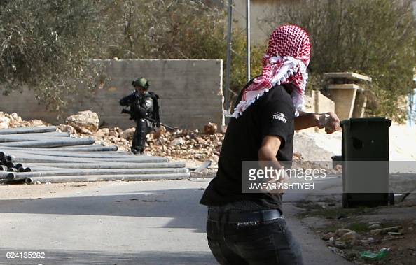 Israeli security forces aim their weapons towards Palestinian protestors throwing rocks during clashes following the weekly demonstration against the...