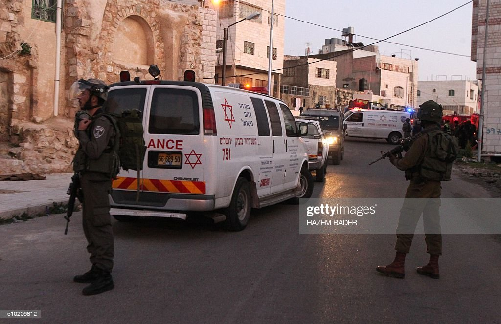 Israeli security forces and ambulances gather at the site of a stabbing attack near the shared religious site known to Jews as the Cave of the Patriarchs and to Muslims as the Ibrahimi Mosque, in the West Bank town of Hebron, on February 14, 2016. A female Palestinian tried to stab an Israeli policeman in the West Bank city of Hebron but was shot and critically wounded, police said, in today's third violent incident. BADER