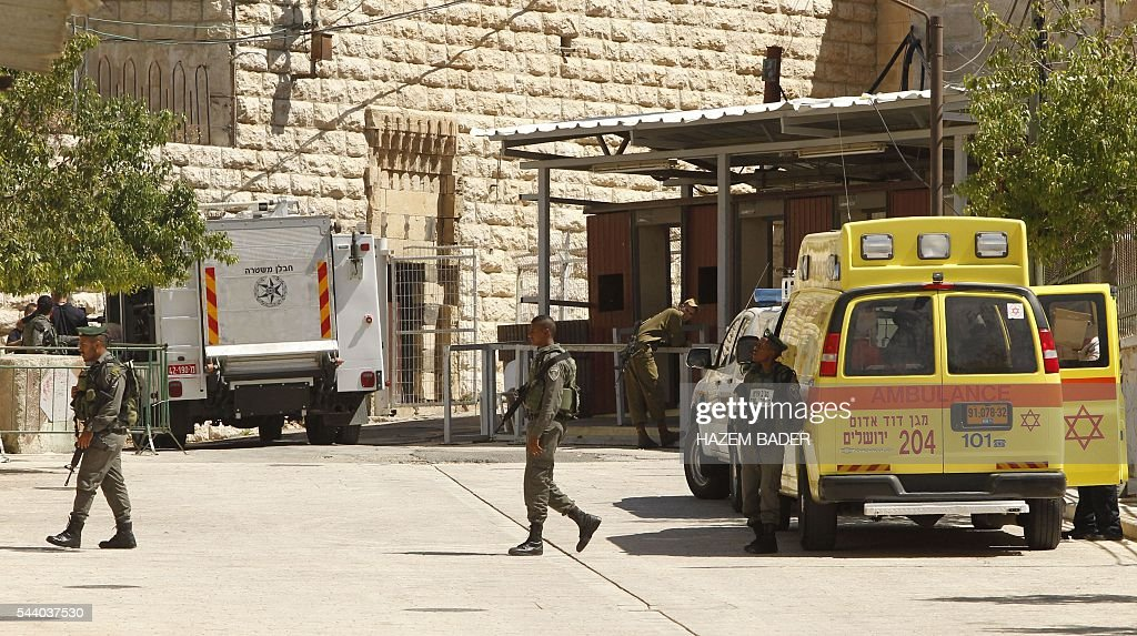 Israeli security forces and emergency personnel are seen on July 1, 2016 near an Israeli checkpoint (L) in the flashpoint West Bank city of Hebron after a Palestinian woman attempted to stab an Israeli guard and was shot dead, according to Israeli police. Israeli authorities said that no police were wounded in the attempt at the site in the southern West Bank city of Hebron, near a religious site known to Muslims as the Ibrahimi Mosque and to Jews as the Cave of the Patriarchs. BADER