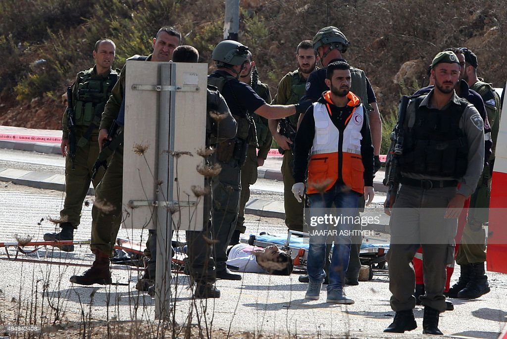 Israeli security forces and emergency personnel stand next to the body of a Palestinian man who was shot dead after allegedly trying to stab Israeli...