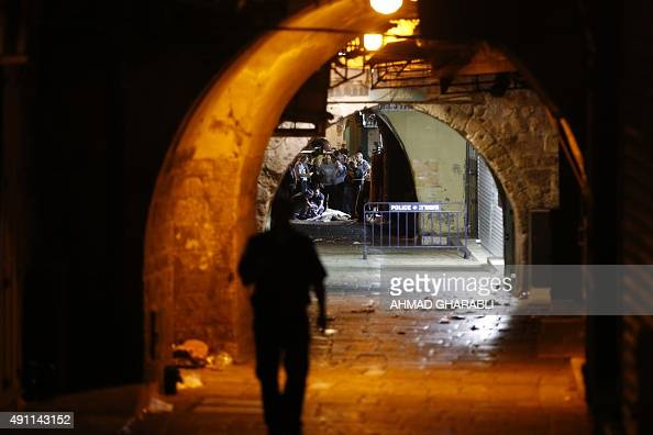 Israeli security forces and emergency services stand next to the body of a Palestinian who carried out a stabbing attack in the old city of Jerusalem...