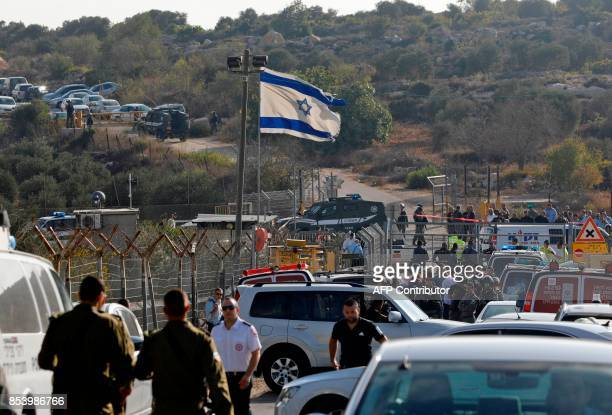 TOPSHOT Israeli security forces and emergency teams gather at the scene of a fatal attack at the entrance to the West Bank settlement of Har Adar...