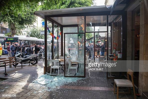Israeli security forces and onlookers stand at the site of an attack by an unidentified gunman who opened fire at a pub in the Israeli city of Tel...