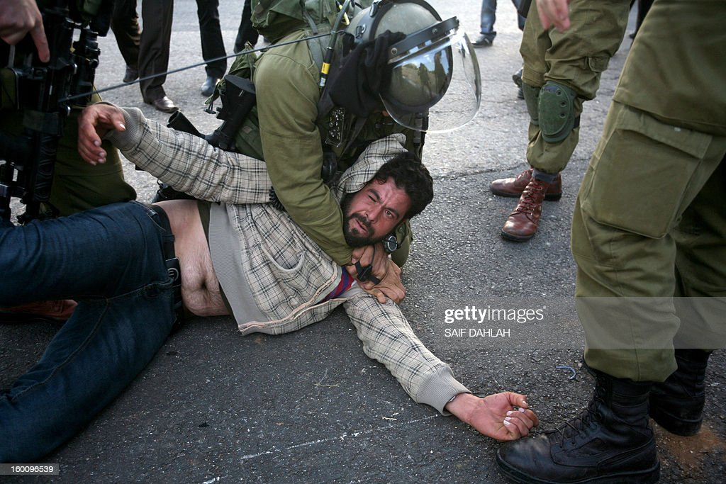 Israeli security forces apprehend a Palestinian demonstrator during a protest in Anin village in the West Bank near Jenin city, on January 26, 2013. Protestors planned to erect a number of tents in solidarity with Palestinian prisoners in Israeli jails, a move they called 'Breaking the constraint'.