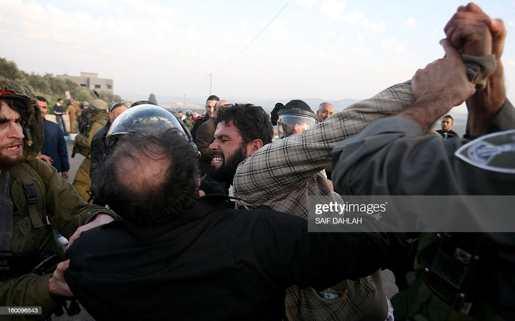 Israeli security forces apprehend a Palestinian demonstrator during a protest in Anin village in the West Bank near Jenin city, on January 26, 2013. Protestors planned to erect a number of tents in solidarity with Palestinian prisoners in Israeli jails, a move they called 'Breaking the constraint'. AFP PHOTO/SAIF DAHLAH