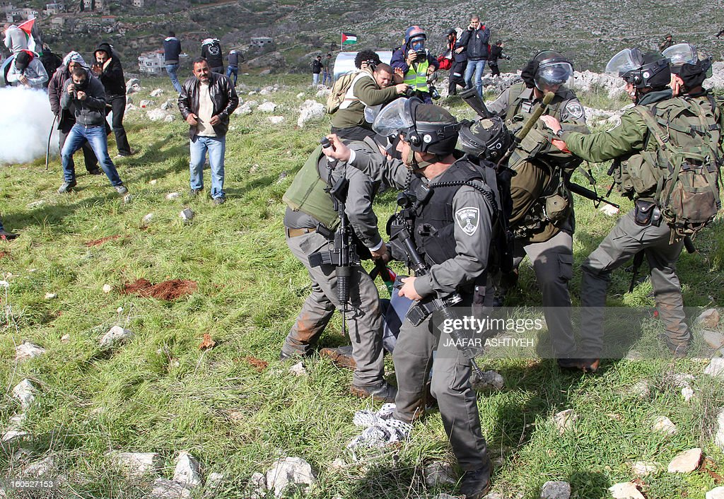 Israeli security forces arrest a Palestinian man as they forcefully remove demonstrators from a new camp set up to protest against Jewish settlements near the West Bank village of Burin on February 2, 2013. An AFP correspondent said the Israeli army used tear gas and violence to remove hundreds of people who had set up four temporary huts and three tents near Burin, south of Nablus in the occupied West Bank, in a third attempt at the novel form of protest against Jewish settlements.