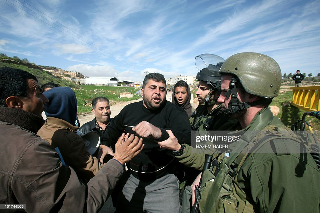 Israeli security forces arrest a Palestinian protestors during a demonstration against the closer of the main southwest entrance of the West Bank city of Hebron, which is situated near the Jewish settlement of Beit Hagai, in the occupied West Bank, on February 15, 2013. AFP PHOTO / HAZEM BADER