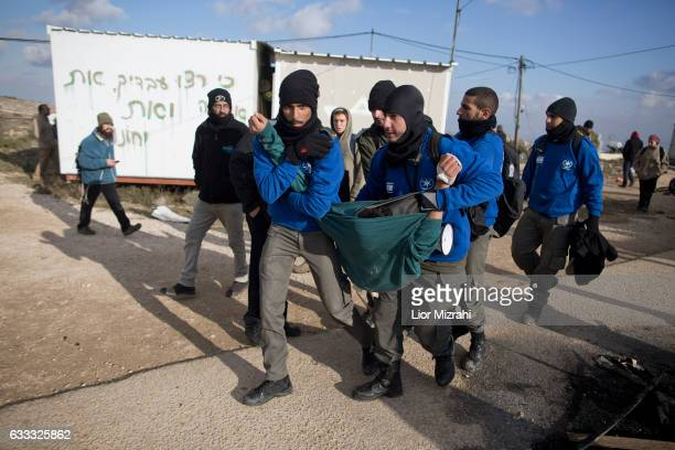 Israeli security forces arrest a settler during the evacuation of an illegal Jewish settlement on February 1 2017 in Amona West Bank Israeli Security...