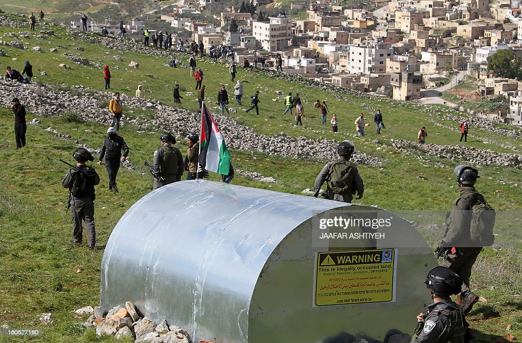 Israeli security forces arrive to remove demonstrators from a new camp set up to protest against Jewish settlements near the West Bank village of Burin on February 2, 2013. An AFP correspondent said the Israeli army used tear gas and violence to remove hundreds of people who had set up four temporary huts and three tents near Burin, south of Nablus in the occupied West Bank, in a third attempt at the novel form of protest against Jewish settlements. AFP PHOTO /JAAFAR ASHTIYEH