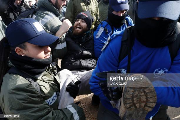 TOPSHOT Israeli security forces carry a settler from the Amona outpost northeast of Ramallah on February 1 2017 as they evict the hardline occupants...