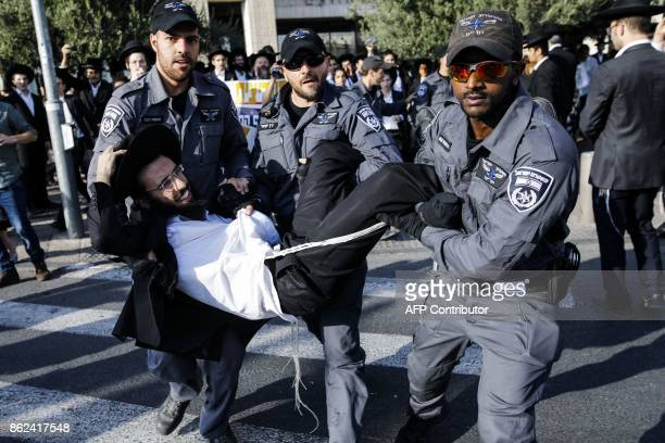 Israeli security forces carry away an UltraOrthodox Jewish demonstrator blocking a main road as they disperse a protest against Israeli army...