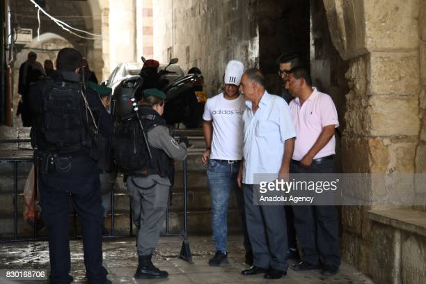 Israeli security forces check IDs of Palestinians as they try to pass security control point at the King Faisal's Gate of Al Aqsa Mosque Compound as...