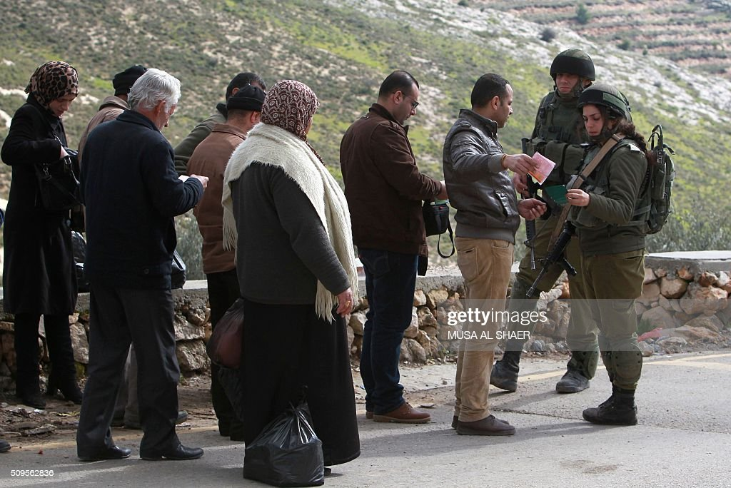 Israeli security forces check the ID's of Palestinians at the entrance of the village of Nahalin southwest of Bethlehem, on February 11, 2016, following its lock down by the Israeli army for a third day as part of efforts to find the perpetrator who stabbed a Jewish man from a nearby settlement earlier in the week. A Jewish man in his twenties had appeared at the entrance to the settlement after having been stabbed while out jogging. He was taken to hospital in moderate condition, with stab wounds in the upper body, medics said. The army said forces were searching the area, but could not immediately determine the nature of the attack. SHAER