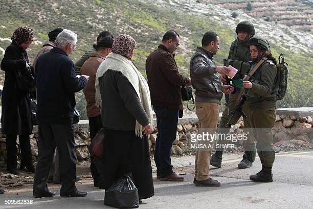 Israeli security forces check the ID's of Palestinians at the entrance of the village of Nahalin southwest of Bethlehem on February 11 following its...