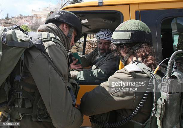 Israeli security forces check the ID's of Palestinians at the entrance of the village of Nahalin southwest of Bethlehem in the Israeli occupied West...