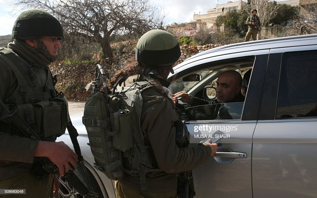 Israeli security forces check the ID's of Palestinians at the entrance of the village of Nahalin, southwest of Bethlehem in the Israeli occupied West Bank, on February 11, 2016, following its lock down by the Israeli army for a third day as part of efforts to find the perpetrator who stabbed a Jewish man from a nearby settlement earlier in the week. A Jewish man in his twenties had appeared at the entrance to the settlement after having been stabbed while out jogging. He was taken to hospital in moderate condition, with stab wounds in the upper body, medics said. The army said forces were searching the area, but could not immediately determine the nature of the attack. SHAER