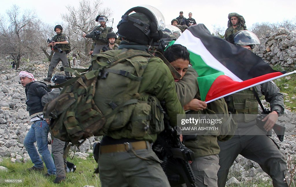 Israeli security forces detain a Palestinian man as they forcefully remove demonstrators from a new camp set up to protest against Jewish settlements near the West Bank village of Burin on February 2, 2013. An AFP correspondent said the Israeli army used tear gas and violence to remove hundreds of people who had set up four temporary huts and three tents near Burin, south of Nablus, in a third attempt at the novel form of protest against Jewish settlements. AFP PHOTO /JAAFAR ASHTIYEH
