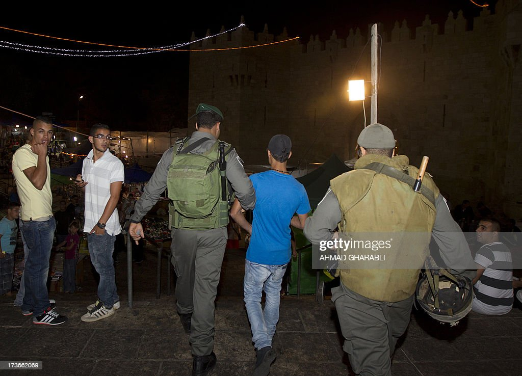Israeli security forces detain a Palestinian youth after an ultra-orthodox Jewish man was stabbed near Damascus gate in the Old City of Jerusalem on July 16, 2013.
