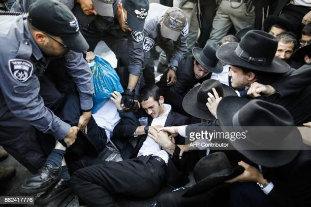 Israeli security forces disperse UltraOrthodox Jewish demonstrators blocking a main road during a protest against Israeli army conscription in the...