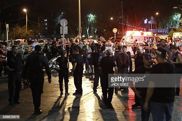 Israeli security forces emergency personnel and civilians are seen at the site of a gun attack in the coastal city of Tel Aviv on June 8 2016 / AFP /...