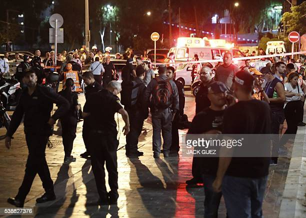 Israeli security forces emergency personnel and civilians are seen at the site of a shooting attack in the Mediterranean coastal city of Tel Aviv on...