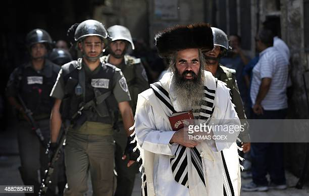 Israeli security forces escort Jewish worshippers coming from the Western Wall Judaism's holiest site as they cross the Muslim quarter in Jerusalem's...