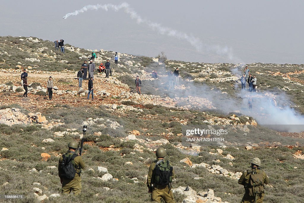 Israeli security forces fire tear gas at Palestinian protestors during clashes in the northern West Bank village of Qusra on January 1, 2013. Israeli security officials have noted a rise in the number of violent incidents in the West Bank since last month's United Nations vote to raise the Palestinians' diplomatic standing.