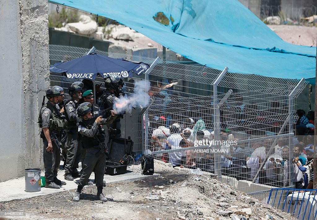 Israeli security forces fire tear gas canisters during clashes with young Palestinians at the Qalandia checkpoint between Ramallah and Jerusalem on July 1, 2016, as Israeli authorities banned men under 45 from accessing the Al-Aqsa mosque compound for Friday prayers. The Palestinian health ministry said that a middle-aged man had died from tear gas fired by Israeli forces during a clash at the Qalandia crossing. / AFP / ABBAS
