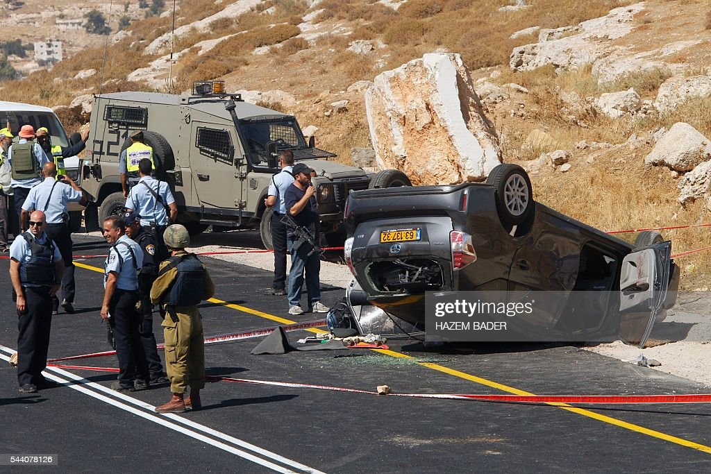 Israeli security forces gather at the scene where an Israeli died and three of his relatives were wounded after a suspected Palestinian gunman opened fire at their car on July 1, 2016 on route 60, near the al-Fawar refugee camp, south of Hebron in the occupied West Bank. The army said troops were 'searching the area for the gunman who fled the scene'. BADER