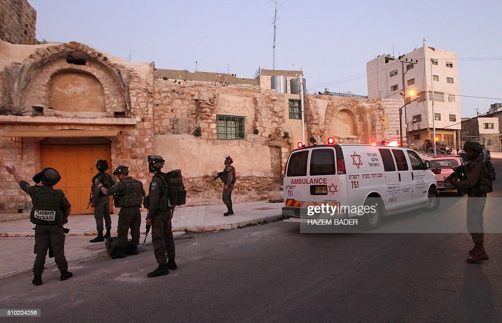 Israeli security forces gather at the site of a stabbing attack near the shared religious site known to Jews as the Cave of the Patriarchs and to Muslims as the Ibrahimi Mosque, in the West Bank town of Hebron, on February 14,2016. A female Palestinian tried to stab an Israeli policeman in the West Bank city of Hebron but was shot and critically wounded, police said, in today's third violent incident. BADER