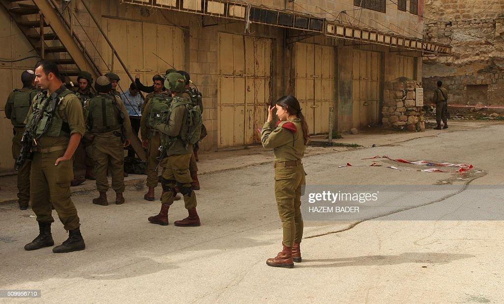 Israeli security forces gather at the site where a Palestinian woman tried to stab an Israeli soldier before being shot dead, in the Israeli occupied West Bank city of Hebron, on February 13, 2016. An Israeli army statement said that 'An assailant drew a knife and attempted to stab a soldier,', 'Responding to the attack, forces fired at the perpetrator, resulting in her death.' The Palestinian health ministry confirmed that a woman was killed but could not immediately give her age or name. The army statement said that the incident occurred near Hebron's shared religious site known to Jews as the Cave of the Patriarchs and to Muslims as the Ibrahimi Mosque, a site of frequent friction between the sides. BADER