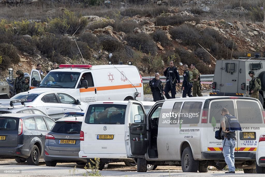 Israeli security forces gather next to the body of a Palestinian man who was shot dead after allegedly trying to stab Israeli police at the Tapuah...