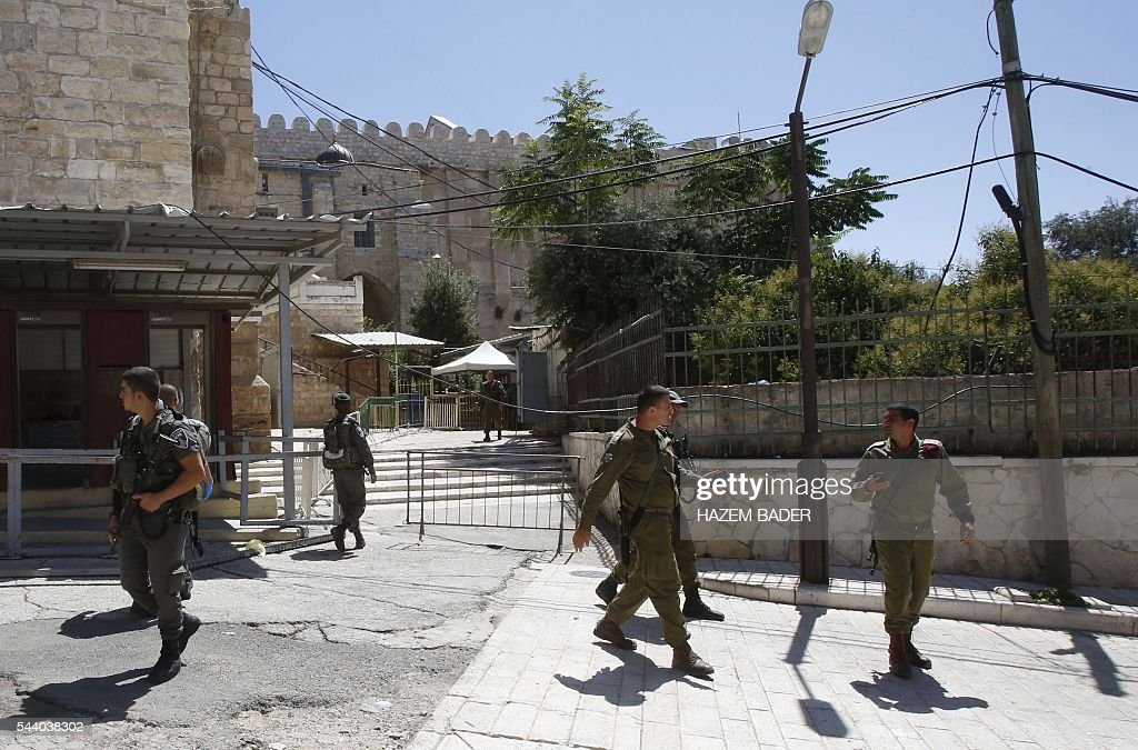 Israeli security forces gather on July 1, 2016 near the entrance of a religious site known to Muslims as the Ibrahimi Mosque and to Jews as the Cave of the Patriarchs, in the flashpoint West Bank city of Hebron after a Palestinian woman attempted to stab an Israeli guard and was shot dead at the site, according to Israeli police. It was the third violent incident in Israel and the Palestinian territories in two days and came as Muslims neared the end of their holy fasting month of Ramadan. BADER