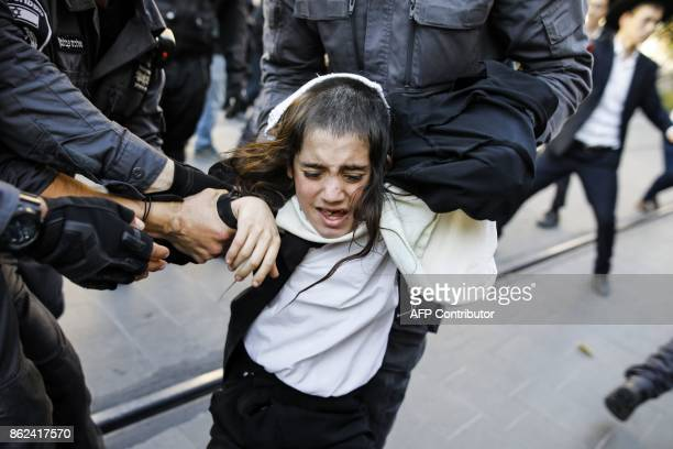 TOPSHOT Israeli security forces grab an UltraOrthodox Jewish boy demonstrator blocking a main road as they disperse a protest against Israeli army...