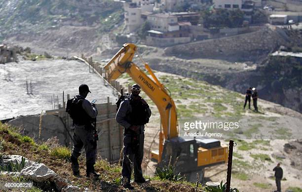 Israeli security forces guard as Israeli bulldozers destroy houses of two Palestinians for allegedly being unauthorized in Jabel Mukaber district of...