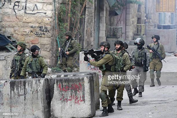 Israeli security forces hold a position during clashes with Palestinian stone throwers following a demonstration to demand Israeli authorities the...
