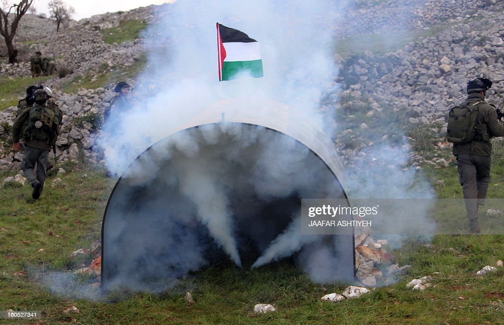 Israeli security forces leave after they fired tear gas in a metal structure as they forcefully remove demonstrators from a new camp set up to protest against Jewish settlements near the West Bank village of Burin on February 2, 2013. An AFP correspondent said the Israeli army used tear gas and violence to remove hundreds of people who had set up four temporary huts and three tents near Burin, south of Nablus in the occupied West Bank, in a third attempt at the novel form of protest against Jewish settlements.