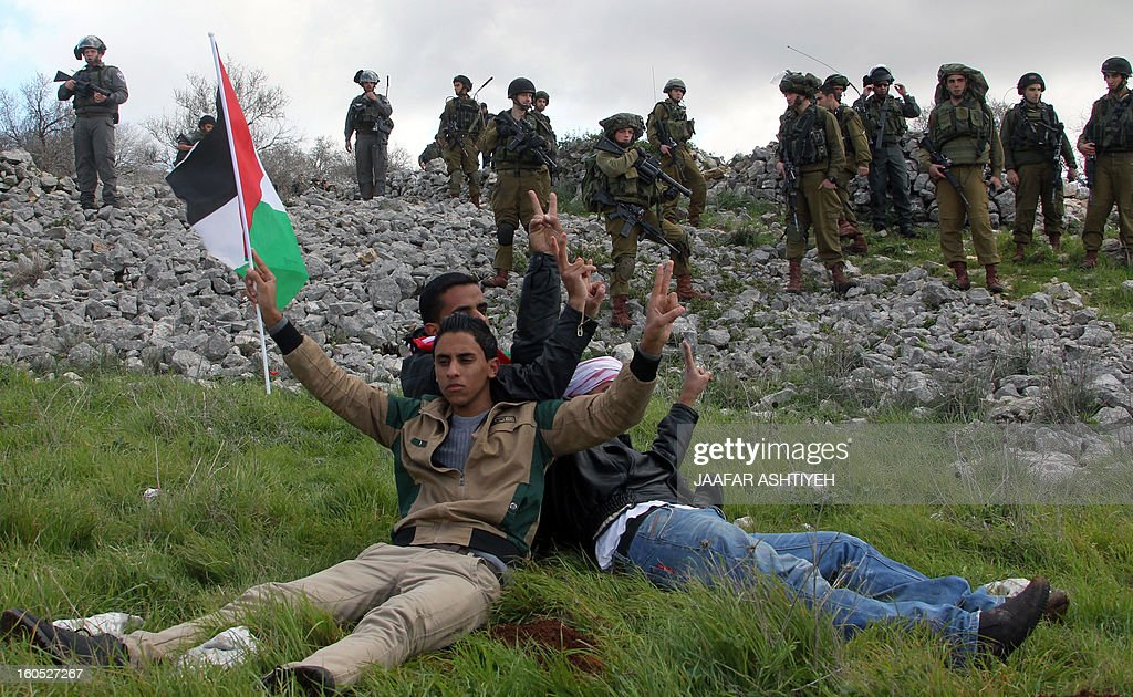 Israeli security forces look at Palestinians sitting flashing the sign of victory at their a new camp set up to protest against Jewish settlements near the West Bank village of Burin on February 2, 2013. An AFP correspondent said the Israeli army used tear gas and violence to remove hundreds of people who had set up four temporary huts and three tents near Burin, south of Nablus in the occupied West Bank, in a third attempt at the novel form of protest against Jewish settlements.