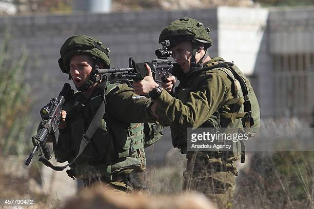 Israeli security forces members stand guard as a group of Palestinians protest the Jewish settlement construction in AlJalzoo region of Ramallah and...