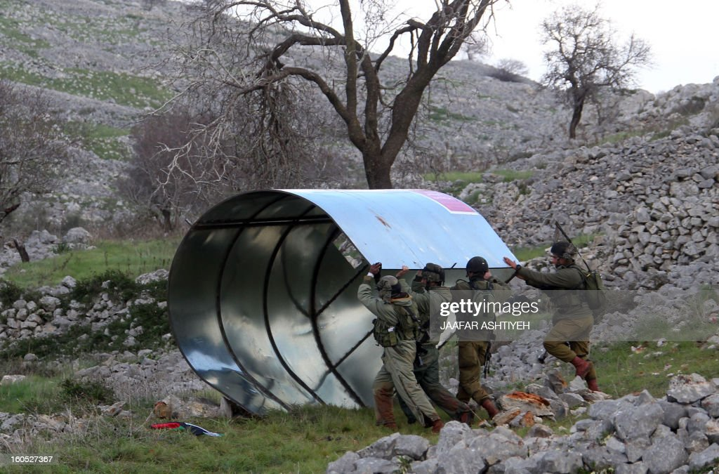 Israeli security forces remove a metal structure put by Palestinians as part their new camp set up to protest against Jewish settlements near the West Bank village of Burin on February 2, 2013. An AFP correspondent said the Israeli army used tear gas and violence to remove hundreds of people who had set up four temporary huts and three tents near Burin, south of Nablus in the occupied West Bank, in a third attempt at the novel form of protest against Jewish settlements.