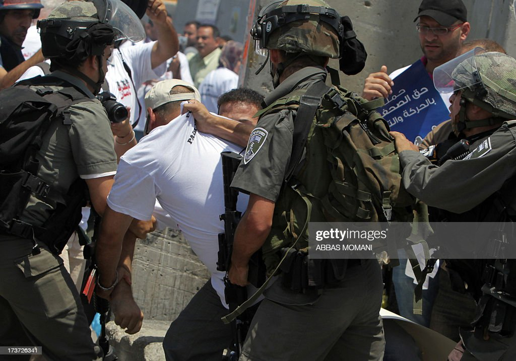 Israeli security forces restrain a protester during a rallye in support of Palestinian journalists who call for freedom of movement on July 17, 2013 at the Qalandia checkpoint between Ramallah and Jerusalem, in the occupied West Bank. AFP PHOTO/ABBAS MOMANI