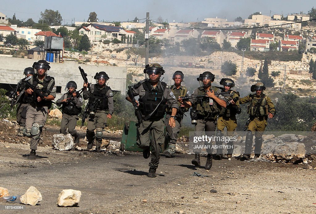 Israeli security forces run after Palestinian protestors during clashes following a demonstration against the expropriation of Palestinian land by Israel in the village of Kfar Qaddum, near Nablus in the occupied West Bank on April 26, 2013.