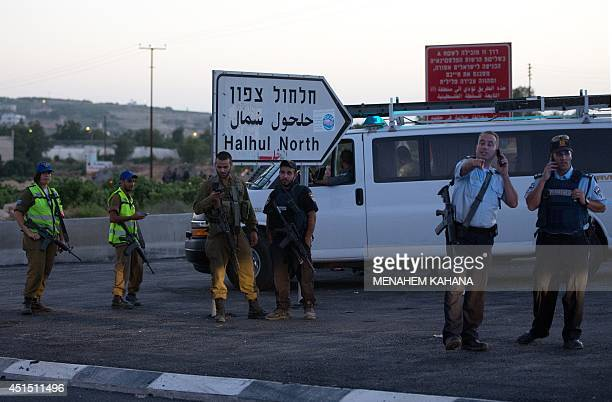 Israeli security forces speak on the phone as they stand guard on June 30 2014 in the village of Halhul near the West Bank town of Hebron where the...