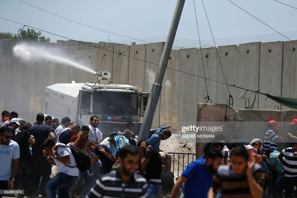 Israeli security forces spray a water cannon towards Palestinian men during clashes at the Qalandia checkpoint between Ramallah and Jerusalem on July 1, 2016, as Israeli authorities banned men under 45 from accessing the Al-Aqsa mosque compound for Friday prayers. The Palestinian health ministry said that a middle-aged man had died from tear gas fired by Israeli forces during a clash at the Qalandia crossing. / AFP / ABBAS